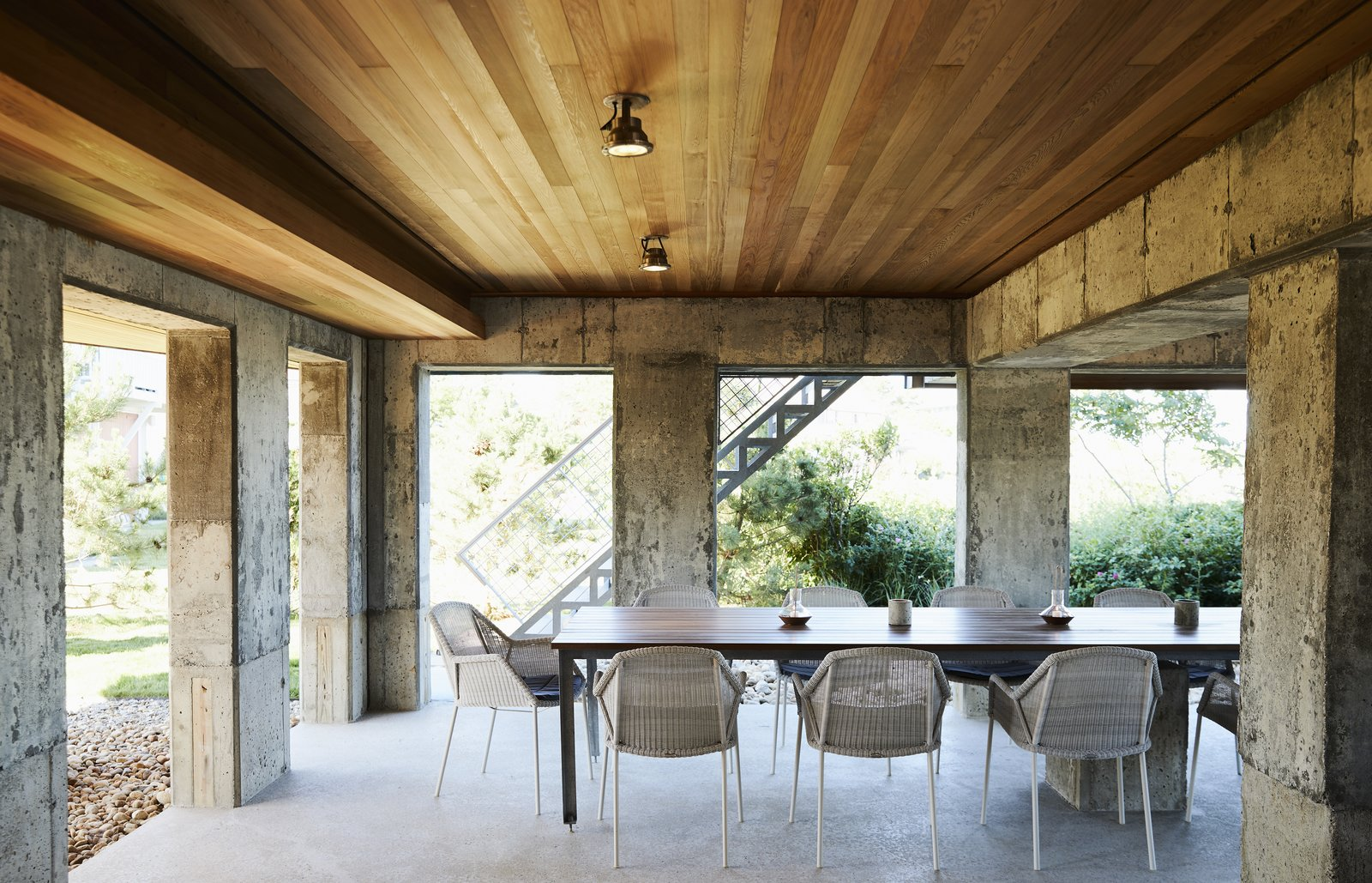 Dining Room, Chair, Concrete Floor, Ceiling Lighting, and Table Once a musty crawl space, the new porch features a custom built-in table and Cane-line Breeze chairs. - Rockport, Massachusetts Dwell Magazine : November / December 2017  Best Photos from On the Coast of Massachusetts, a Prefab Ranch Is Totally Overhauled for a Wheelchair-User
