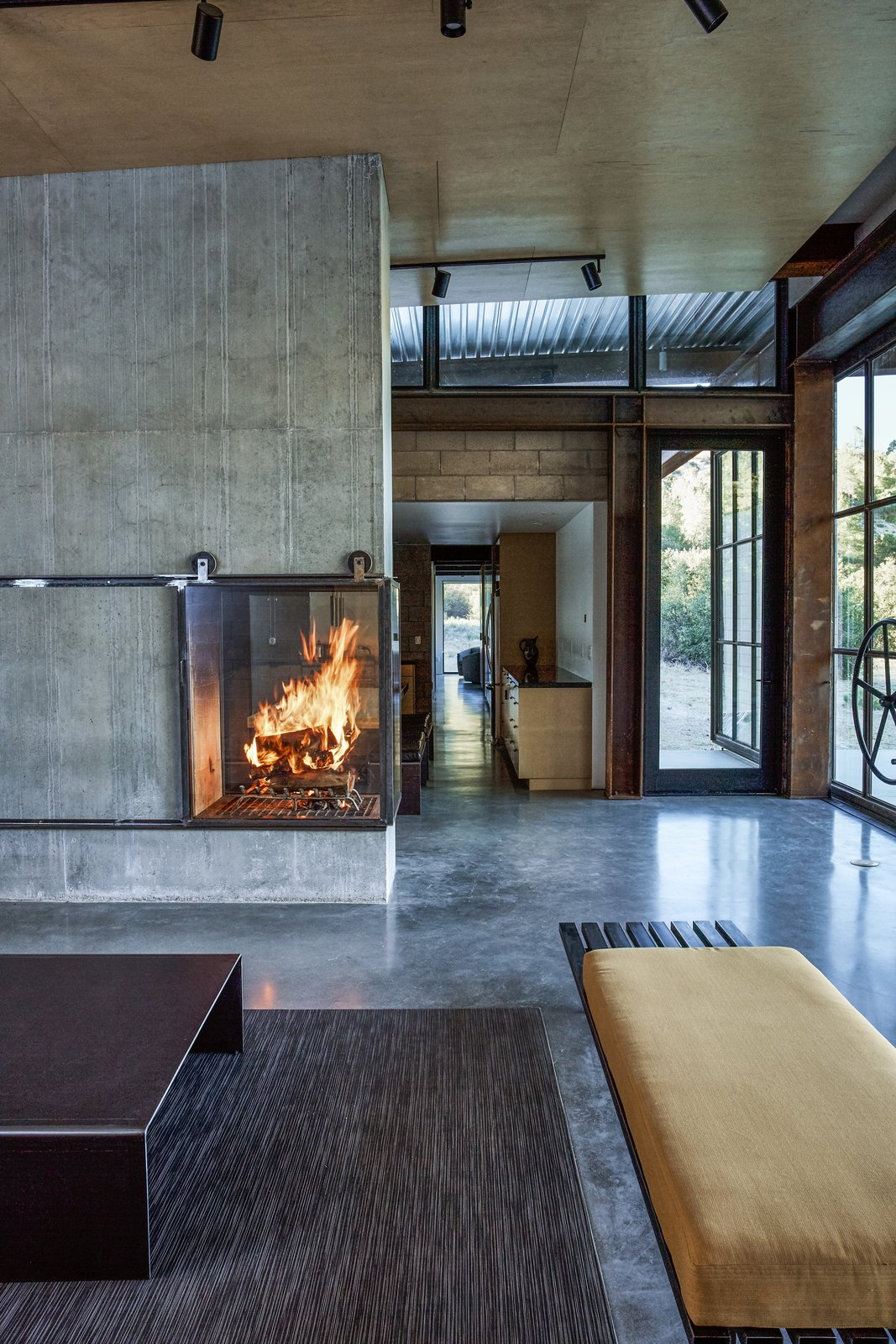 Living Room, Corner Fireplace, Wood Burning Fireplace, Concrete Floor, Bench, and Rug Floor Inspired by Russian and Finnish designs, the fireplace harvests hot air by sending it into the basement and radiating it into the room. - Tehachapi Mountains, California Dwell Magazine : November / December 2017  Photos from At This High-Desert Home, a Whole Wall Opens Up When You Crank a Giant Wheel
