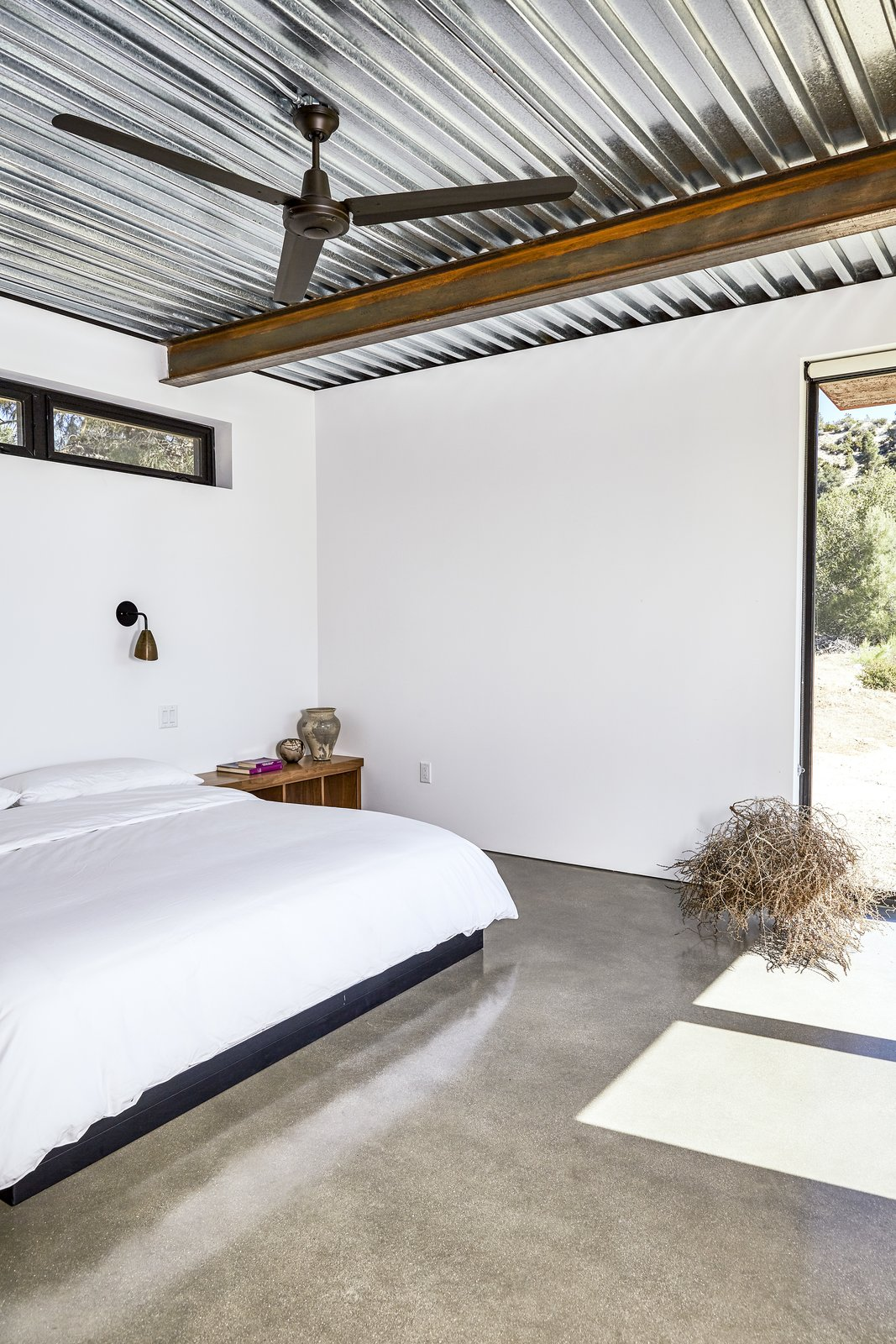 Bedroom, Bed, Concrete, Wall, and Night Stands The master bedroom occupies one of three units extending off the main space. Like other furnishings, the bed was made by steel fabricators. - Tehachapi Mountains, California Dwell Magazine : November / December 2017  Best Bedroom Night Stands Wall Concrete Photos from At This High-Desert Home, a Whole Wall Opens Up When You Crank a Giant Wheel