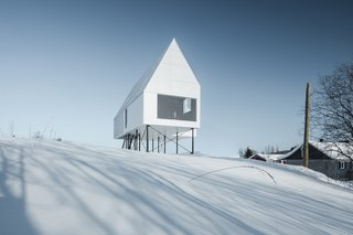 White concrete panel cladding and corrugated steel roof panels give this cabin a crisp, geometric form that almost melts into the landscape on bleary, snowy days.