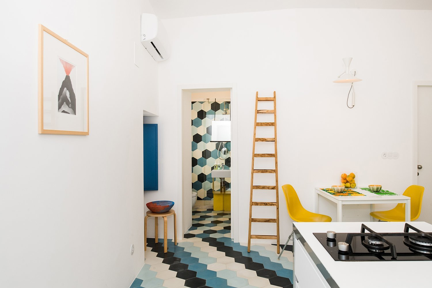 Dining Room, Stools, Chair, Table, Ceramic Tile Floor, and Wall Lighting The combined kitchen and dining space is compact yet efficient.  Photo 2 of 13 in An Old Fisherman's House in Sicily Is Transformed Into 2 Apartments