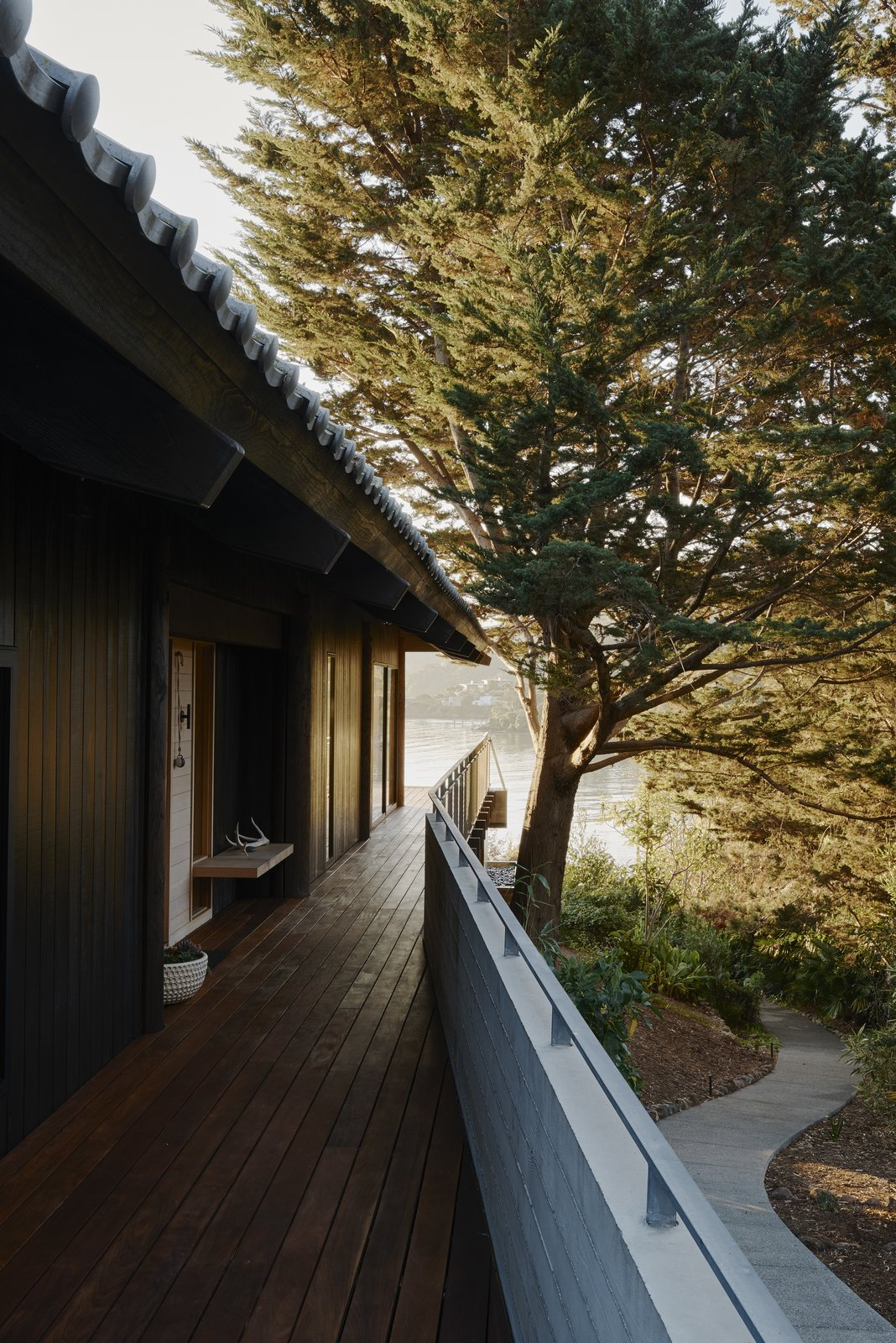 Outdoor, Shrubs, Walkways, Trees, Side Yard, and Wood Patio, Porch, Deck Prentis Hale of SHED Architecture & Design reimagined a kit home in Tiburon, California, that was erected in 1991. Photo:  Photo 1 of 13 in You'd Never Guess This Japanese-Style Home in Tiburon Is a Kit House