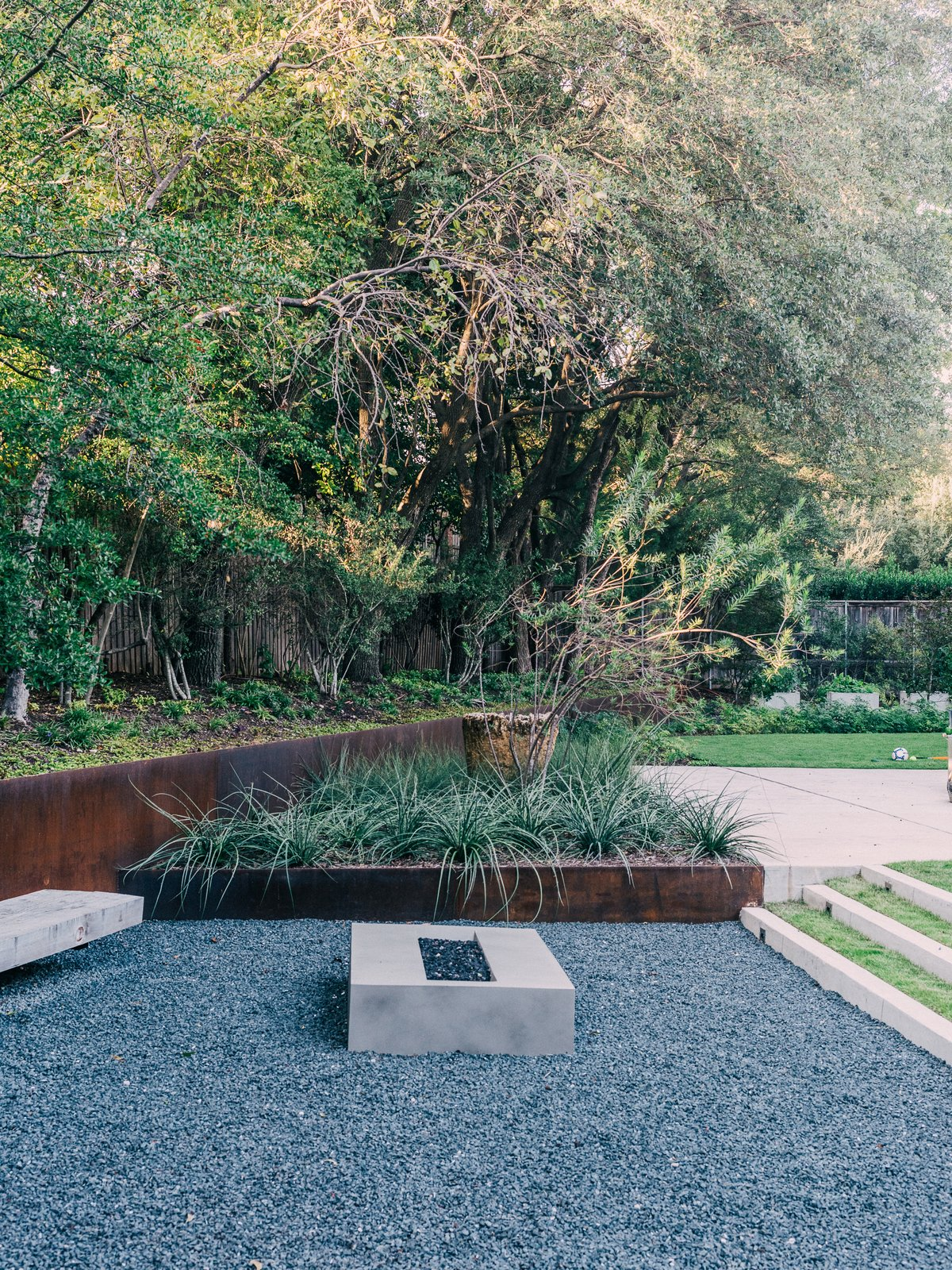 Outdoor, Garden, Gardens, Walkways, Concrete Patio, Porch, Deck, Grass, Hardscapes, Shrubs, and Trees Behind her is the greenhouse, where Lynn starts vegetables like lettuce, Swiss chard, and tomatoes. Landscape architect David Hocker defined the sunken fire pit area with Cor-Ten steel.  Best Photos from A Black Stucco Home in Dallas Is Surrounded by Eye-Popping Greenery