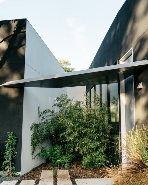 """The entrance to the house is marked by a triangular awning. """"It's just enough to protect the front door,"""" says Merrill, """"and then  it sheds water into a small garden between the garage and the house."""""""