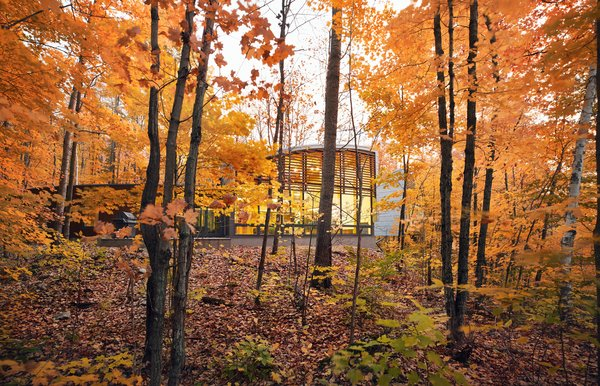 "Clad in SPF lumber, zinc, and glass, David Bronskill and Mark Dilworth's vacation home on Oblong Lake fans out to capture wide views of the forest. ""Nothing is straight in the plan,"" says architect Roland Rom Colthoff of RAW Design, who conceived the 2,500-square-foot escape. From left to right, there are three structures: a three-bedroom guest wing, a voluminous communal area, and a semi-detached master suite. Two of the wings share an unusual fin-shape design because of their varied ceiling heights."
