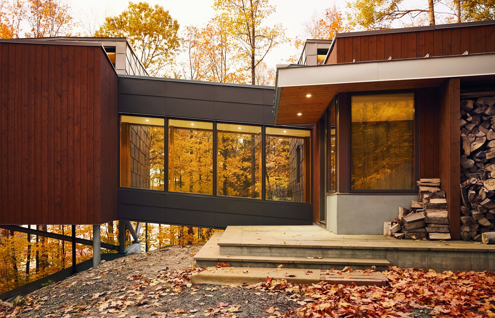Exterior, Glass Siding Material, House Building Type, Metal Siding Material, and Wood Siding Material Set on a steel frame and reached by a bridge, the master suite extends up to 13 feet above the sloping grade.  Photos from A Curved House in Ontario Bends 100 Degrees for Forest Views