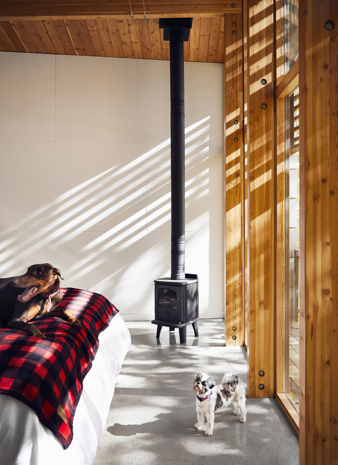 Bedroom, Concrete Floor, and Bed The master suite is warmed by a Badger 3112 woodstove by Morsø.  Best Photos from A Curved House in Ontario Bends 100 Degrees For Forest Views