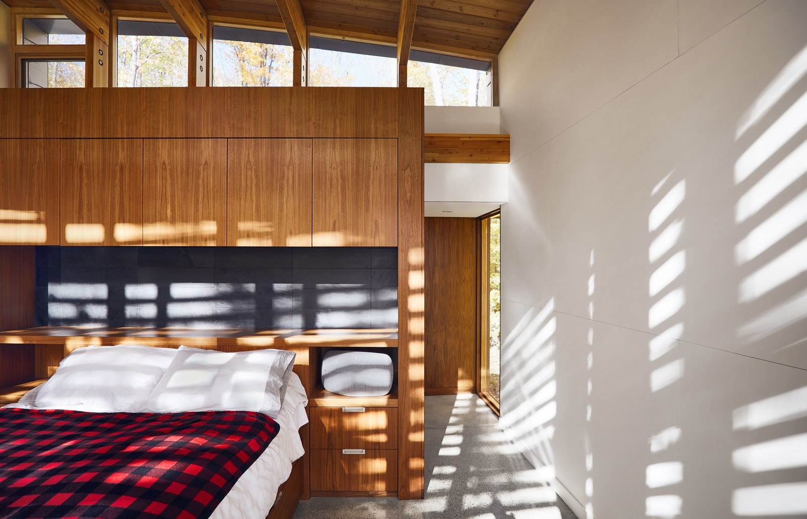 Bedroom, Storage, Bed, and Terrazzo Walnut ply millwork by Ashley Woodturning and polished concrete floors with radiant heating appear throughout the residence.  Best Bedroom Terrazzo Bed Photos from A Curved House in Ontario Bends 100 Degrees For Forest Views