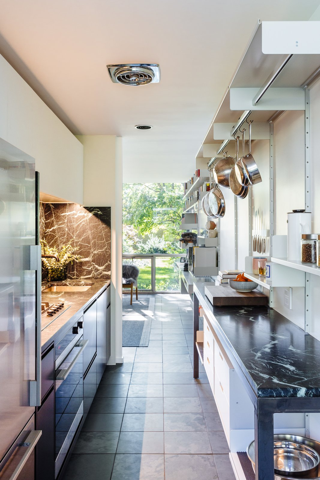 Kitchen, Marble, Refrigerator, White, Range, Undermount, Slate, Accent, and Marble Designer Bryan Boyer and lawyer Laura Lewis bought their townhouse in Lafayette Park in 2015, the same year the storied co-op joined the National Register of Historic Places. Their restoration included laying slate floor tiles the same size as the original linoleum squares, hanging modular Dieter Rams wall shelving, and adding appliances by Fisher & Paykel.  Best Kitchen Marble Slate Photos from A New York Transplant Remakes One of Mies van der Rohe's Coveted Townhouses in Detroit
