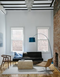On the top floor, a Cumberland chair by Thos. Moser faces a Room & Board ottoman, a Twiggy lamp by Foscarini, and a vintage sofa upholstered in cowhide.