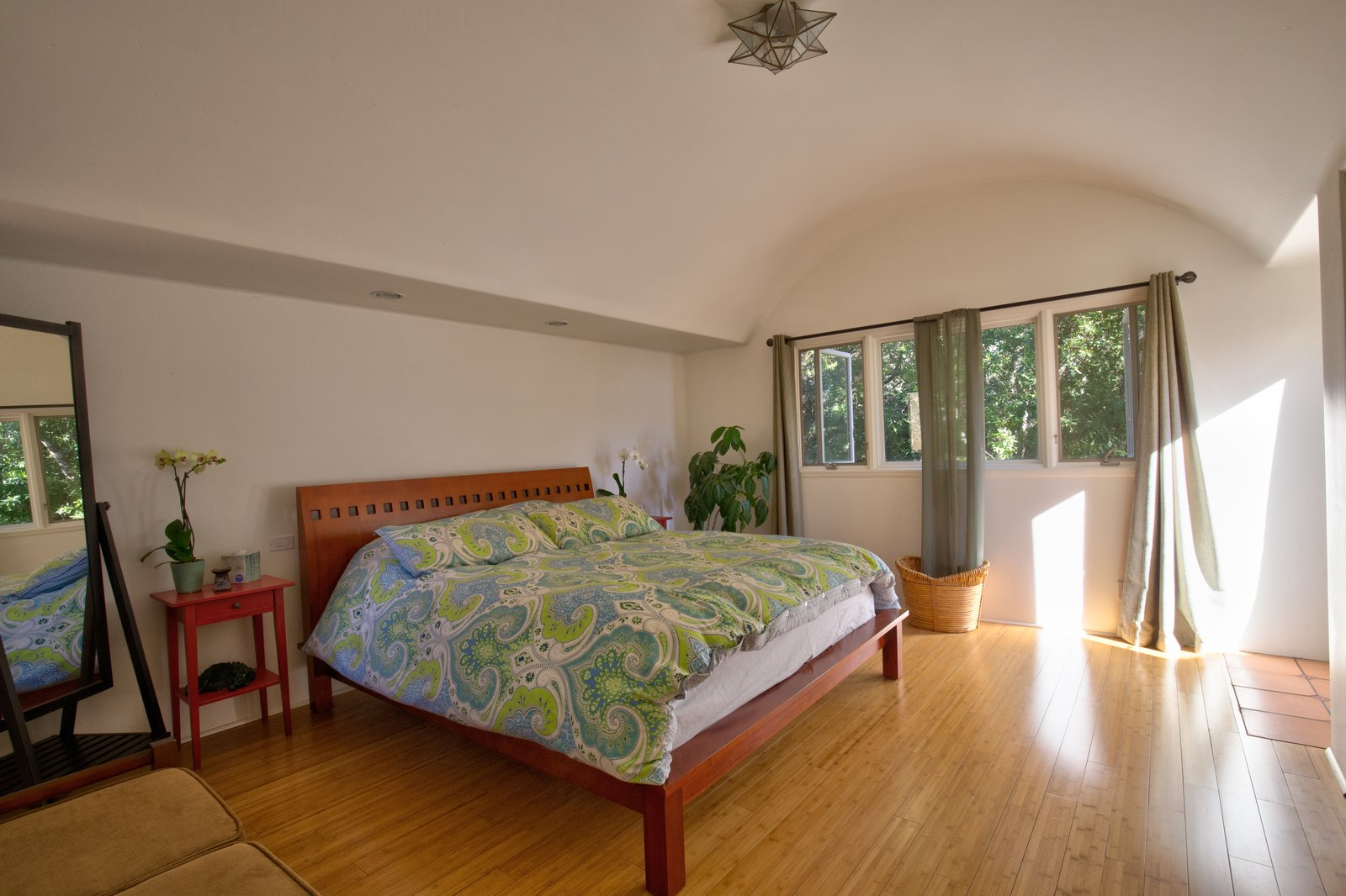 Bedroom, Medium Hardwood Floor, Ceiling Lighting, Night Stands, and Bed The main bedroom has a generous closet and outdoor access.  Photo 8 of 10 in This Santa Barbara Yurt Is the Ultimate Place to Recharge