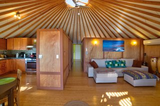 The exposed beams of the yurt lead up to a central skylight that helps the space feel bright and airy.