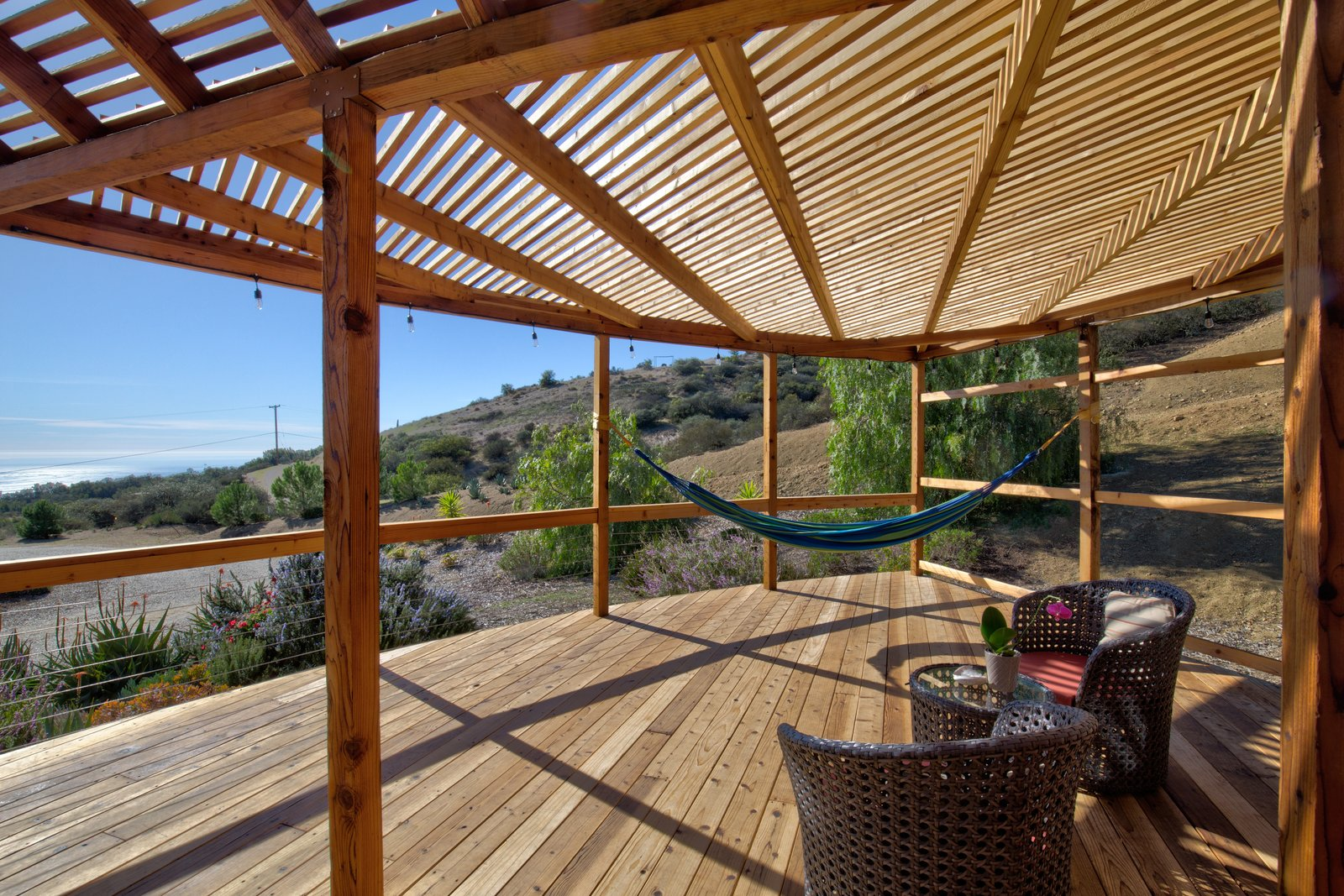 Outdoor, Wood Patio, Porch, Deck, Front Yard, Wire Fences, Wall, Desert, Decking Patio, Porch, Deck, Trees, and Shrubs The deck has multiple lounge spaces, including two hammocks, and would make for an inspiring, open-air yoga studio.  Photo 3 of 10 in This Santa Barbara Yurt Is the Ultimate Place to Recharge