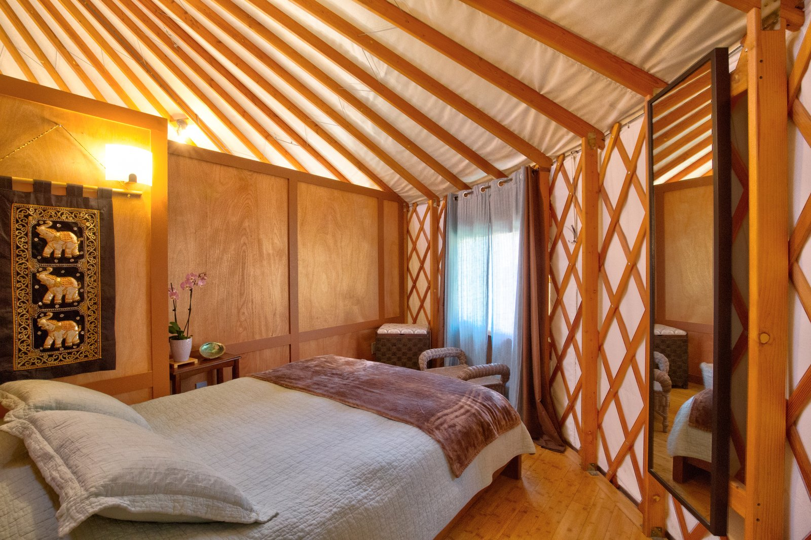 Bedroom, Medium Hardwood Floor, Wall Lighting, Bed, and Night Stands The smaller bedroom is tucked behind a partition for privacy.  Photo 7 of 10 in This Santa Barbara Yurt Is the Ultimate Place to Recharge