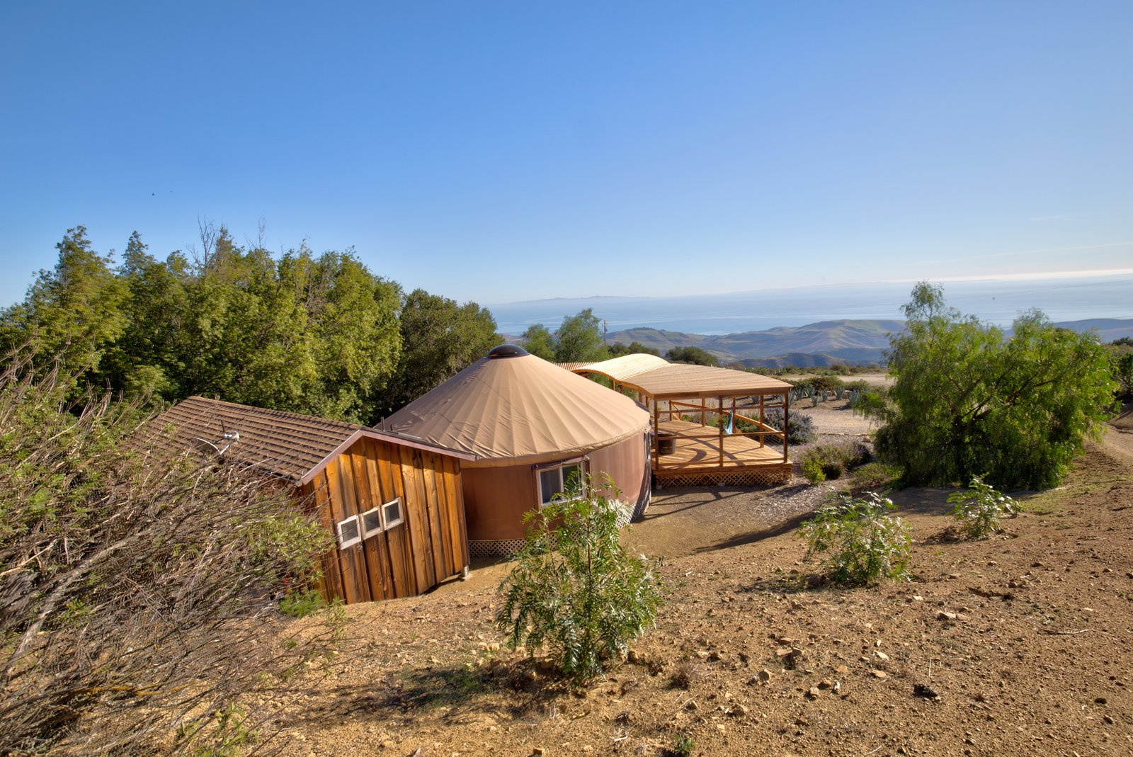 Outdoor, Desert, Trees, Decking Patio, Porch, Deck, Wood Patio, Porch, Deck, Hardscapes, Shrubs, and Back Yard The customized yurt, attached hut, and porch are perched atop Refugio Mountain for stunning views.  Photo 10 of 10 in This Santa Barbara Yurt Is the Ultimate Place to Recharge