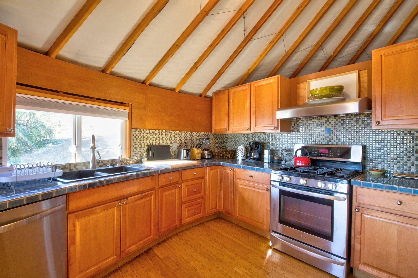 Kitchen, Drop In Sink, Range, Tile Counter, Mosaic Tile Backsplashe, Medium Hardwood Floor, Wood Cabinet, Wall Oven, and Range Hood The roomy kitchen offers all the comforts of home.  Photo 6 of 10 in This Santa Barbara Yurt Is the Ultimate Place to Recharge