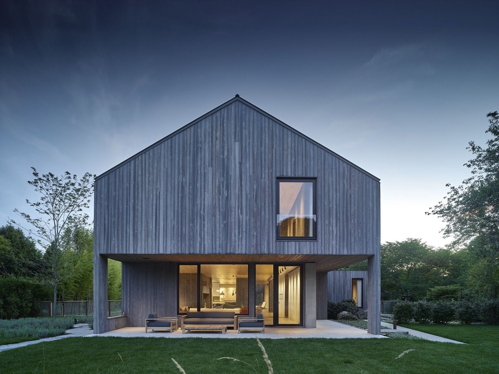 Outdoor, Back Yard, Small Patio, Porch, Deck, Grass, and Trees A peek at the home from a distance.  Best Photos from This Stunning Suffolk County Home Brings a Modern Twist to a Historic Area