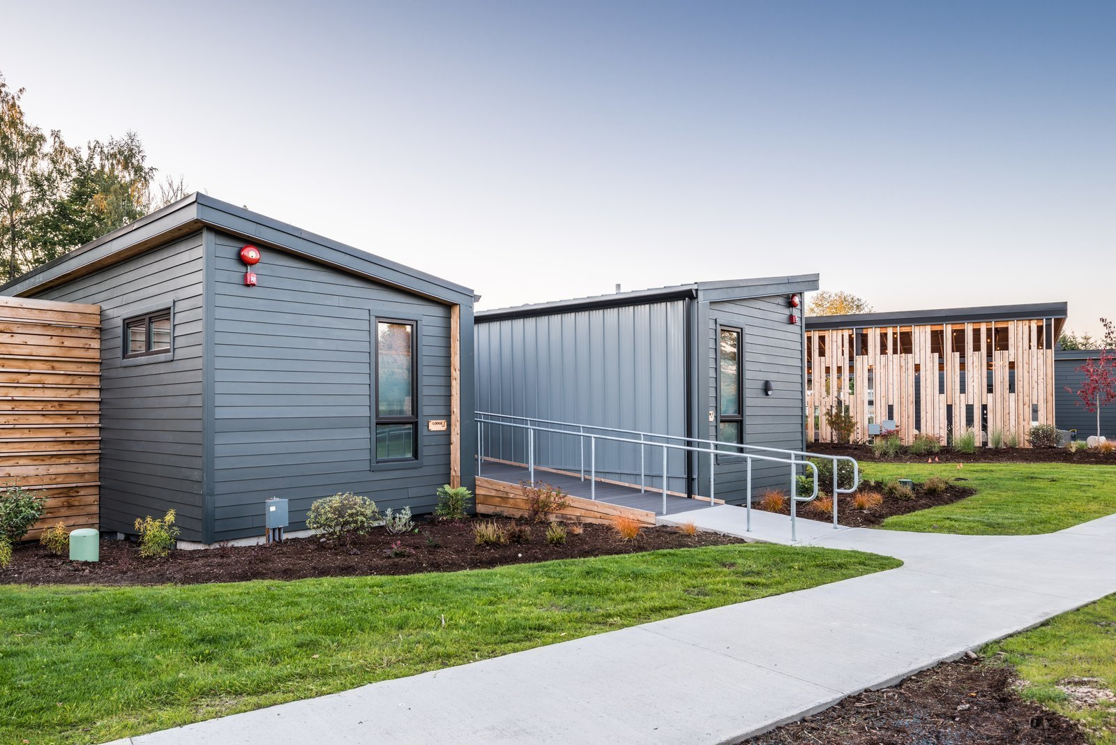 Exterior, Prefab Building Type, Cabin Building Type, Wood Siding Material, and Shed RoofLine Paved walkways connect each unit to the public spaces.  Photo 7 of 7 in Serenity Awaits at These Prefab Cabin Rentals on Vashon Island