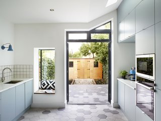 """A Small Studio came up with a plan to transform their 53-square-foot kitchenby filling in the """"side return,"""" a narrowoutdoorspace that is a feature of many Victorian terrace homes. These spaces were designed to allow in daylight and, once upon a time, provide access to an outside toilet and coal bunker. In the backyard, the couple installed a shed for storing their bicycles. The window seat was an item on homeowner Emma Boyd's wish list."""
