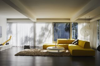 In keeping with Viks's design, the living room remains on the second floor. A bright yellow artwork by Ken'ichiro Taniguchi complements the Bend Sofa by Patricia Urquiola for B&B Italia. The Random pendant lights are by Bertjan Pot for Moooi, the Yo-Yo coffee table is by Emanuele Zenere, and the Maltino Rug is by Linie Design. The hardwood flooring is from the Admiration line by Mirage.