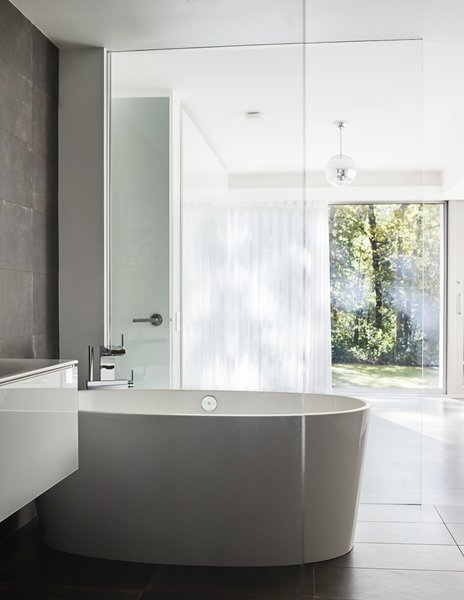 The bathtub is by Victoria + Albert and the Terre Ruggine tiles are by Iris Ceramica.