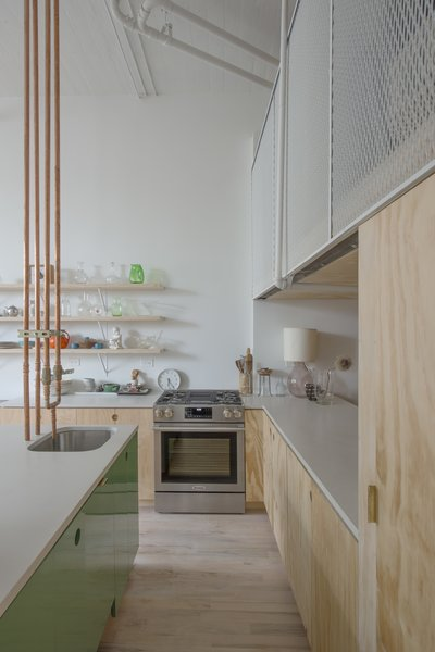 The sink's copper pipes were rerouted to come down from the ceiling instead of up through the cabinets. Some of the storage units have lacquered MDF faces.