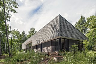 "Vince and Adrienne Murphy's rural retreat is clad in gray shingles and gray-stained pine. ""They wanted the cottage to meld into the woods and be visually quiet,"" says architect Kelly Doran, who worked with Portico Timber Frames to build the 2,500-square-foot home."