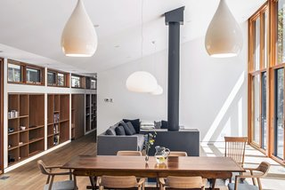 The furniture is a combination of family heirlooms and newer items, such as the Hiroshima Woodseat armchairs by Naoto Fukusawa for Mjolk that surround the dining table. Two Glo-Ball pendants by Jasper Morrison hang in the living/dining area, while Drop 1 pendants by Peter Bowles light the kitchen.
