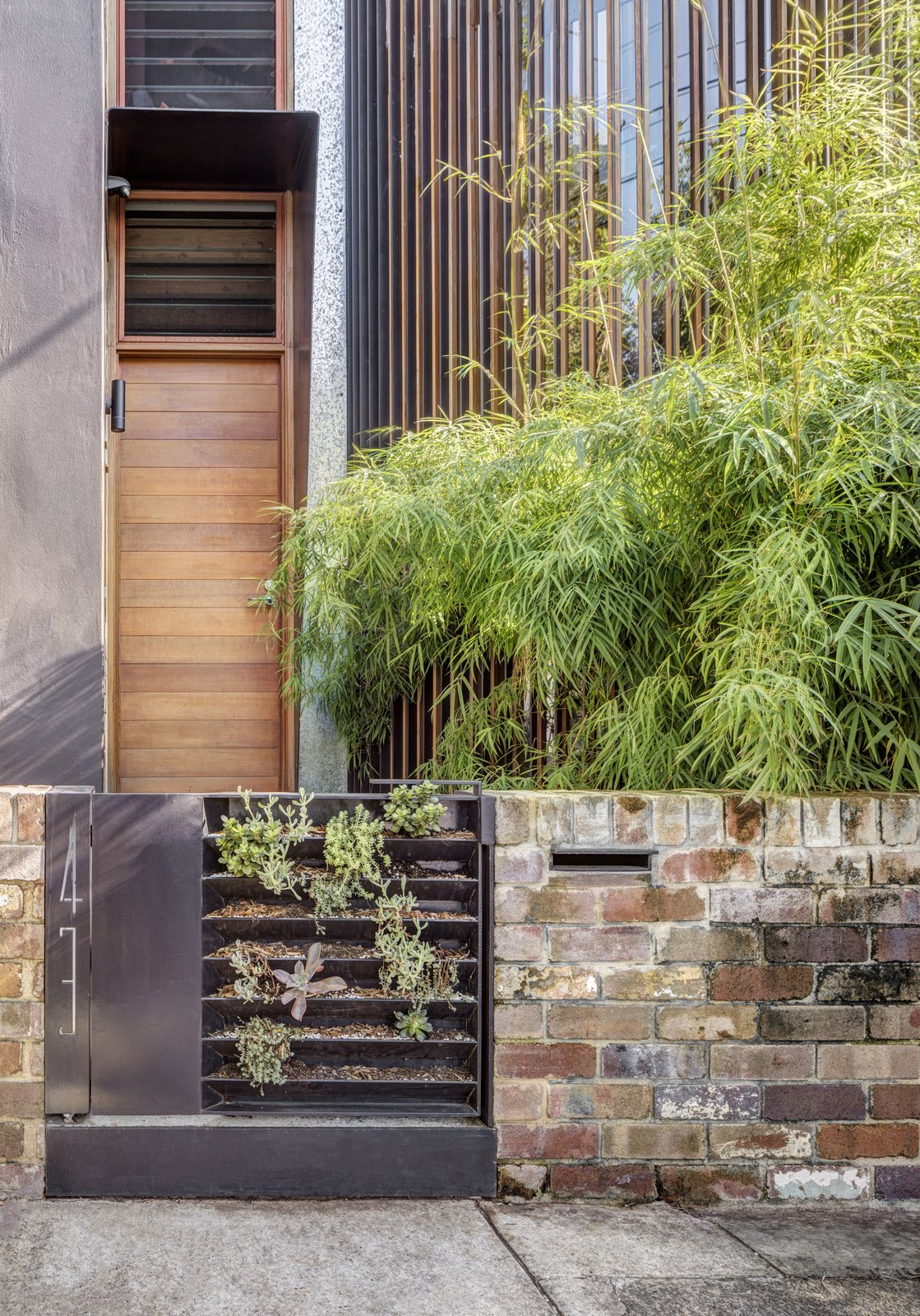Exterior, Concrete Siding Material, Wood Siding Material, House Building Type, and Stone Siding Material The gate leading to Geoff Carroll and Julie Young's rebuilt terrace house in an inner suburb of Sydney, Australia, holds an array of succulents, signaling what lies within:  a greenery-filled home that includes a central courtyard, vertical gardens, aquaponics and rain filter systems, and even a chicken coop. Architect Clinton Cole of CplusC Architectural Workshop led a team of collaborators in revamping the property.  Aquas Perma Solar Firma from A Sustainable Home Near Sydney Boasts Chicken Coops, Vertical Gardens, and More