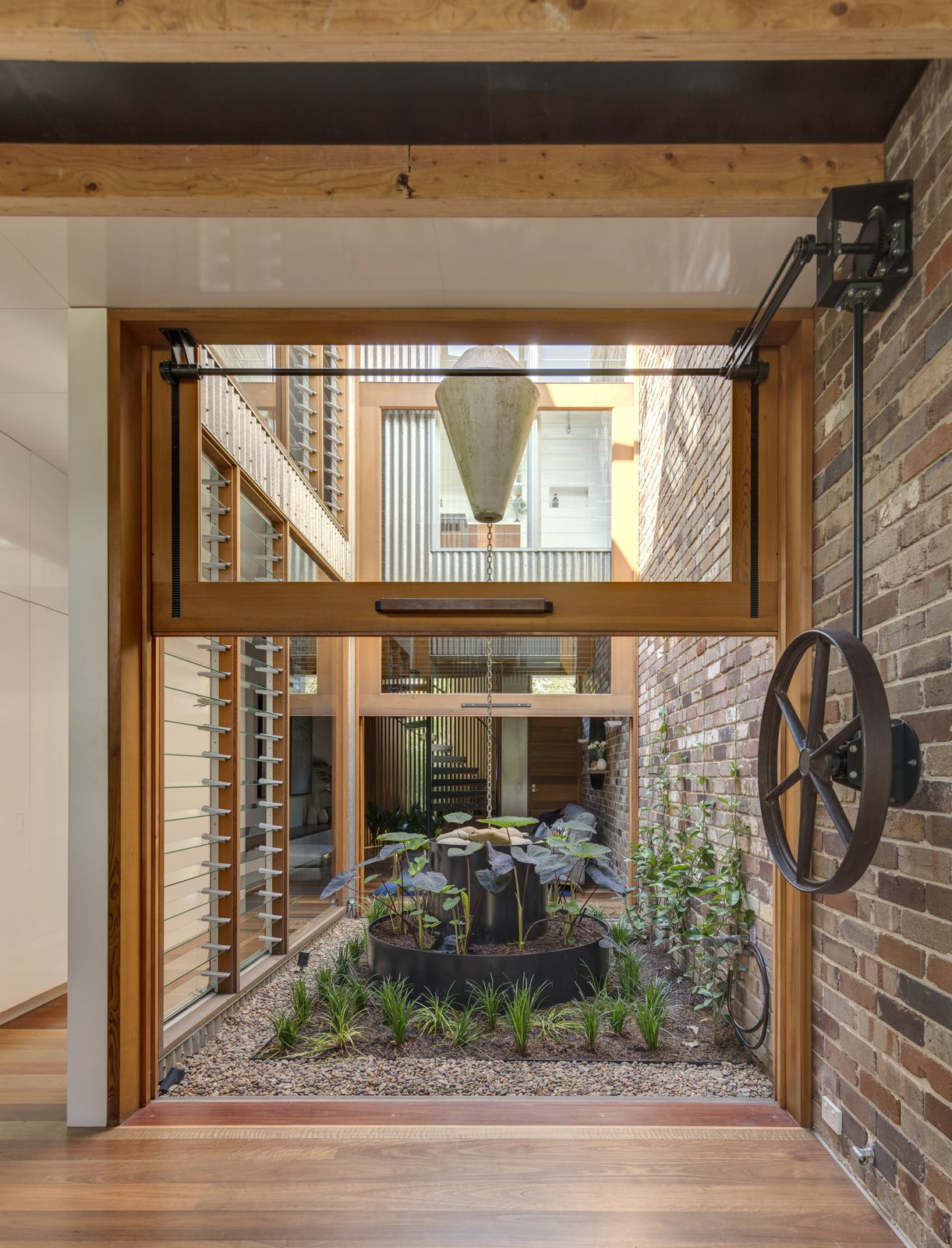 Outdoor, Gardens, and Garden A counterweight pulley system makes easy work of lifting the large glazed walls flanking the courtyard.  Photo 2 of 9 in A Sustainable Home Near Sydney Boasts Chicken Coops, Vertical Gardens, and More