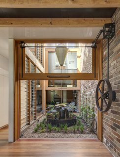A counterweight pulley system makes easy work of lifting the large glazed walls flanking the courtyard. Brick walls extend from the home's interior out into the courtyard.