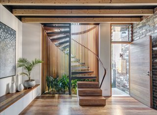 A cylindrical glass staircase with Western red cedar and painted steel mullions dominates the front of the house. The stair treads, along with the floor, are made of recycled spotted gum.