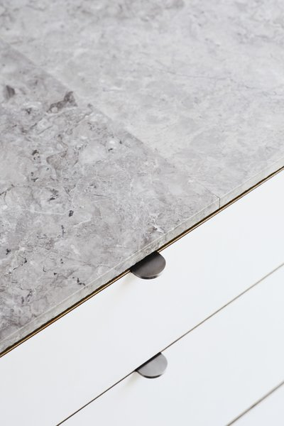 """<b>Kitchen Countertops: </b>The Jacks saved about $6,500 by skipping counter-sized marble  slabs and using one-by-two-foot marble tiles, sealed with silicone. """"The counters are thin and highly polished, but the sides have a rough texture,"""" Beer observes."""