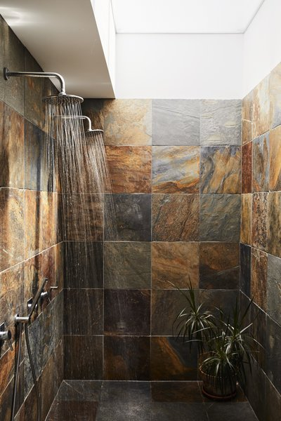 Covered in slate squares from Cambridge Tile, the master bathroom includes a double shower  with rain heads by M&Z Rubinetterie. A skylight lets in natural light while maintaining the residents' privacy.