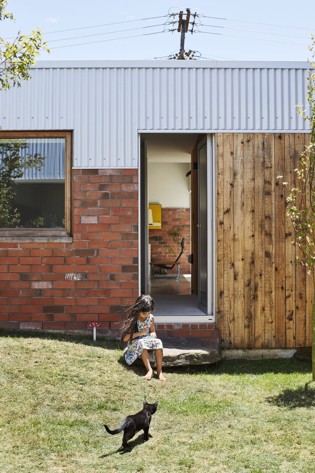 "In the middle courtyard, the Jacks landscaped a small grass mound for Sadie, five, to play on. The house is topped with corrugated steel. ""It's essentially the cheapest material you can get for roofing in New Zealand,"" says Beer."