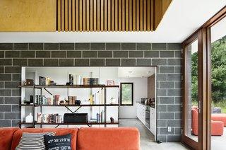 A vintage shelving unit provides storage and hallway separation.
