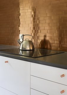 In the kitchen, copper-colored stainless steel tiles from TileBar create a glowing backsplash that is offset by the neutral white cabinets. The cabinetry is by IKEA, the countertop is Caesarstone, and the induction cooktop is by Bosch.