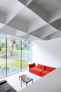 A villa in Leuven, Belgium, has an unusual new roof over its garden extension. Instead of being flat on the underside, the steel structure varies in thickness from about 2 inches to 18 inches (with an 8-inch layer of insulation on top). As the ceiling dips, the floor drops: The living area is four steps below the rest of the room. Fix lights from Lucide hang from above. The Highlands sofa is by Patricia Urquiola.