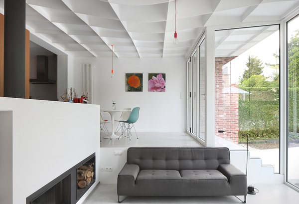 A half wall with a fireplace by Kalfire creates division within the space.