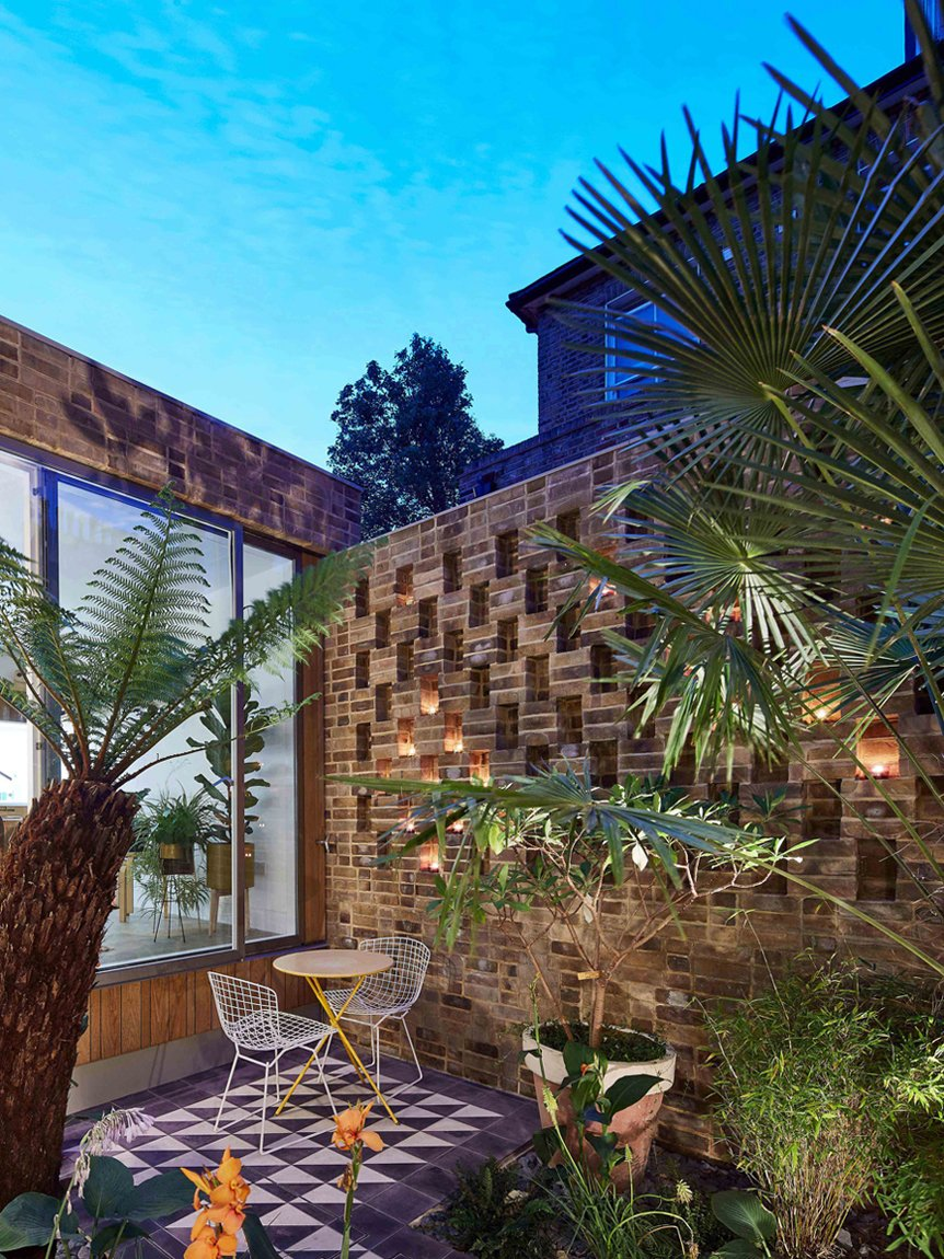 A view into the exterior courtyard. Its tile floor mimics the tile treatment at the entry for cohesion and the perforated brickwork creates a lovely pattern when backlit at night.