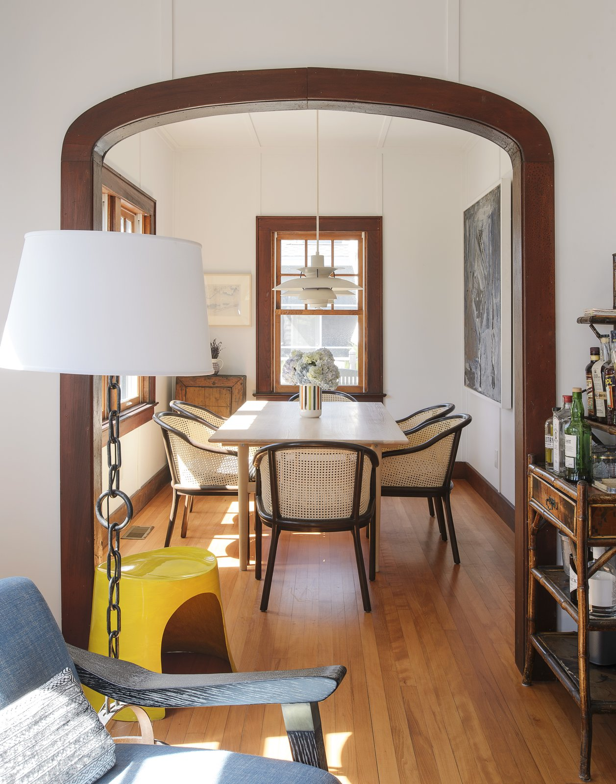 Dining Room, Medium Hardwood Floor, Floor Lighting, Pendant Lighting, Chair, and Table In the dining room, there's a Poul Henningsen pendant, a Hans Wegner table, and Ward Bennett Landmark chairs.  Best Photos from This Eclectic Beach Bungalow on Fire Island Was Saved After Sandy