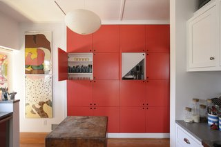 Architect Eric Schiller built storage units underneath the stairs in the kitchen and had them painted Geranium by Benjamin Moore.
