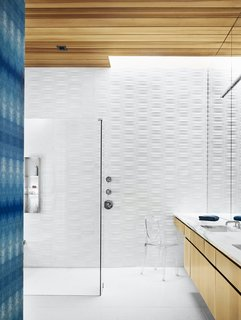 The bathroom is covered in Heath tile and indigo Eskayel wallpaper. The Ghost chair is by Philippe Starck.