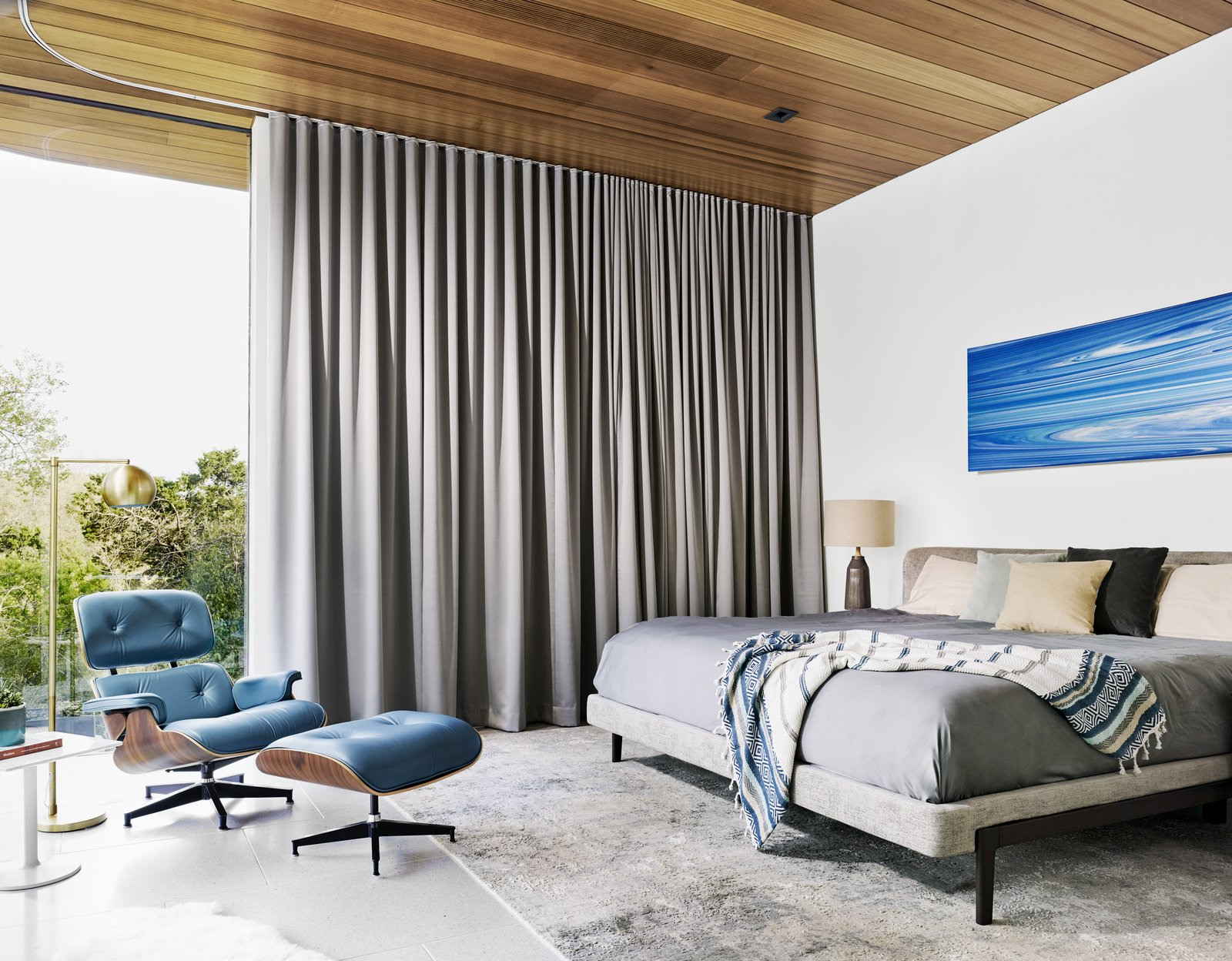 Bedroom, Bed, Table, Floor, Chair, Rug, and Terrazzo Drapes by Cush Cush Design offer privacy in the master bedroom. An Andy Moses painting hangs above the bed.  Best Bedroom Terrazzo Bed Photos from Cover Story: This House in Austin Has a Tree Growing Right Through It