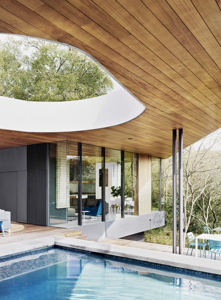 A second aperture in the roof is located over the shallow end of the pool. An alfresco dining area, with seating by Kettal, is perched a few steps below.