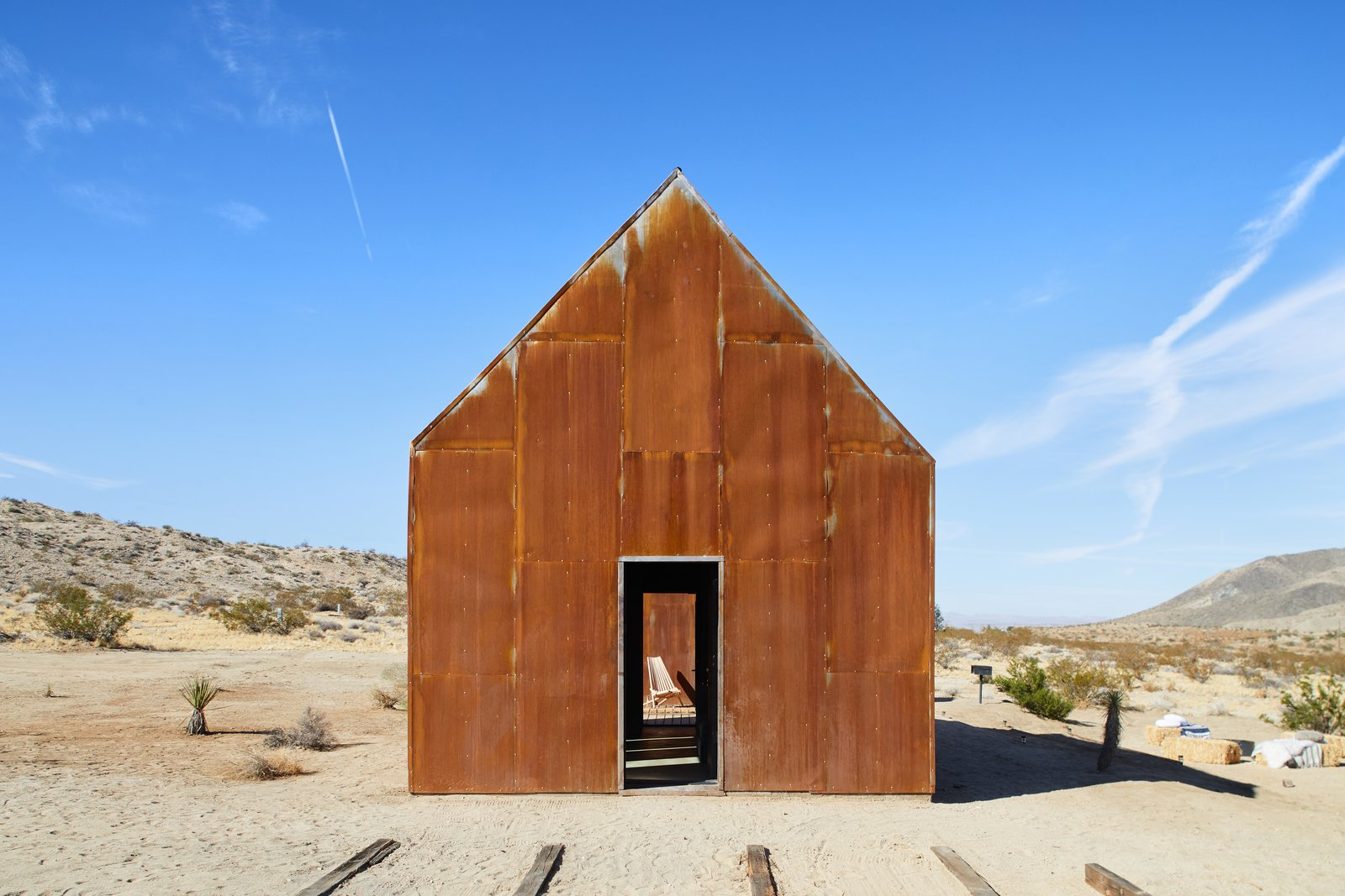 "Exterior, Gable RoofLine, Cabin Building Type, Metal Roof Material, and Metal Siding Material Naturally rusted steel sheathes the cabins that Malek Alqadi built on a 1954 homestead outside Joshua Tree National Park. ""I loved the idea of stitching the existing structure back together, reinforcing it, and giving it life again without compromising the beautiful setting it's in,"" he says.  Photo 1 of 13 in These Tiny, Off-the-Grid Cabins Near Joshua Tree Look Totally Apocalypse-Proof"