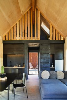 Raw plywood contrasts with dark plaster in the 460-square-foot main cabin, whose communal space encompasses an efficient living/dining area and kitchen.