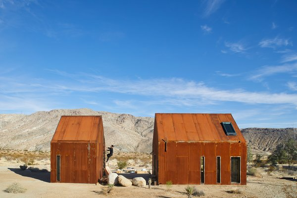 Surrounded by boulders and twisted yuccas, these two cabins in the Mojave Desert stand like Monopoly houses, with their steel siding weathered to a tawny finish. But behind the simple gabled forms lies a complex network that enables them to operate wholly off the grid.