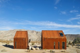 At first glance, the Folly cabins may appear to be a pair of abandoned sheds, left to rust amidst the desert landscape. Within their walls, however, is a modern dwelling swathed in raw plywood with a living space, dining area, kitchen, bathroom, and sleeping mezzanine. A soaking tub anchors a wooden deck; and just up the stairs is a stargazing portal. The off-grid cabins were created by architectural designer Malek Alqadi, who has a penchant for sustainable living.