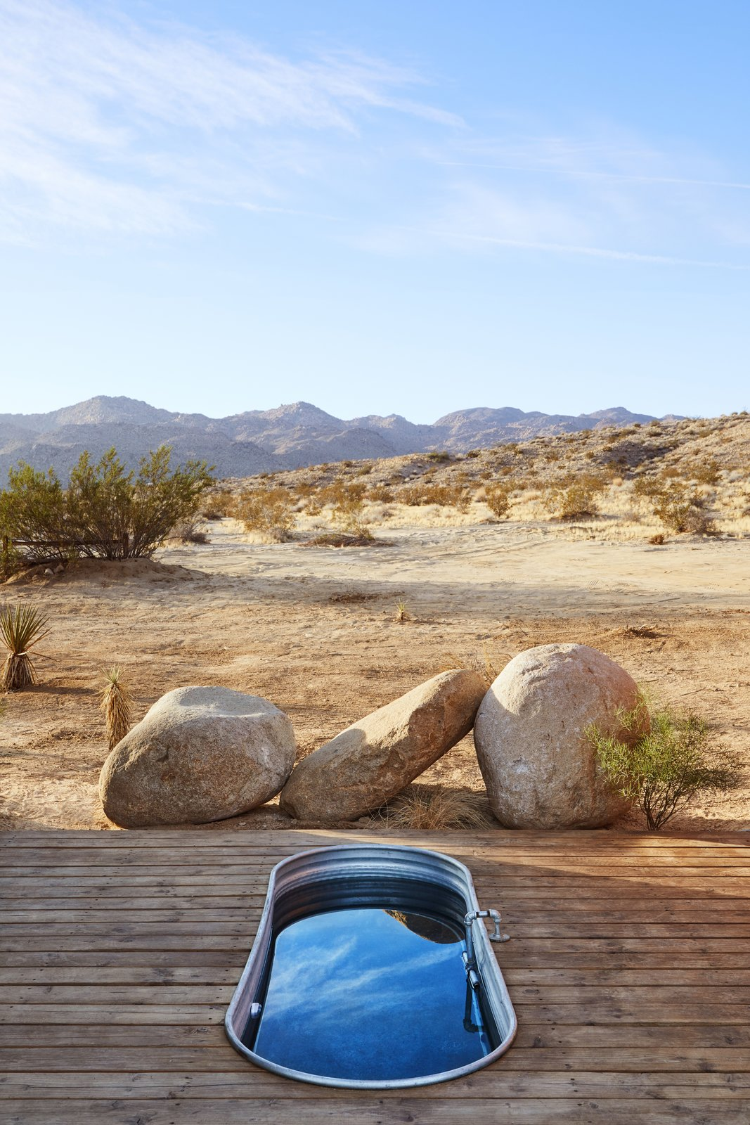 Outdoor, Desert, Wood, Boulders, and Hot Tub The deck connecting the two buildings has an outdoor rain shower and a soaking tub, both part of the property's gray-water system.  Best Outdoor Boulders Hot Tub Photos from These Tiny, Off-the-Grid Cabins Near Joshua Tree Look Totally Apocalypse-Proof